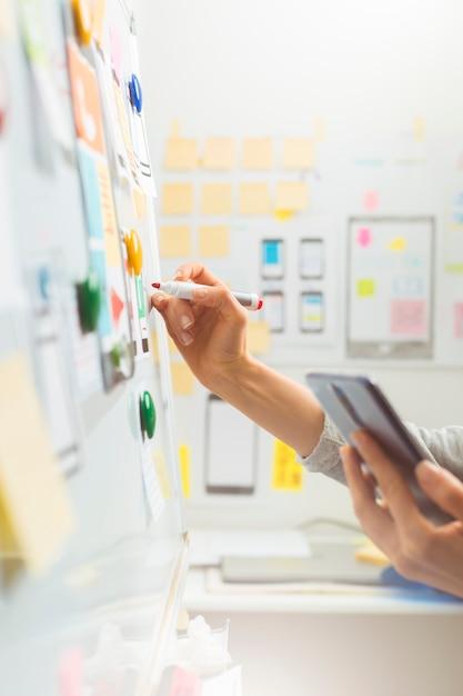 Un diseñador dibuja un boceto de un proyecto de sitio web. desarrolladores de interfaces de aplicaciones móviles. Foto Premium