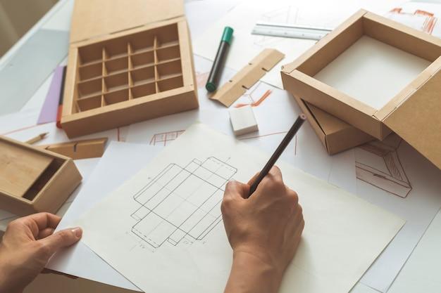 El diseñador dibuja bocetos para envases de cartón. Foto Premium