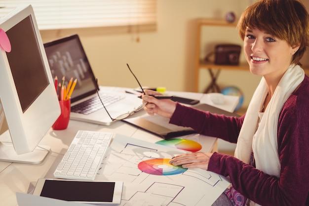 Diseñador gráfico trabajando en escritorio en oficina Foto Premium