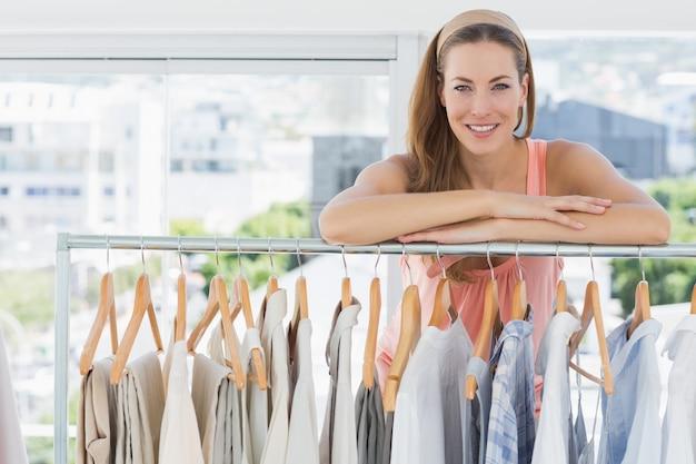 Diseñador de moda femenina con estante de ropa en la tienda Foto Premium