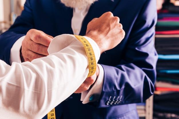 Un diseñador de modas masculino que mide el gemelo de su cliente. Foto gratis