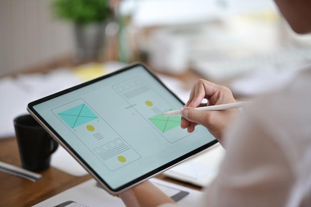 Diseñador que utiliza la planificación de tabletas wireframe en un sitio web móvil, desarrollo de aplicaciones ux ui Foto Premium