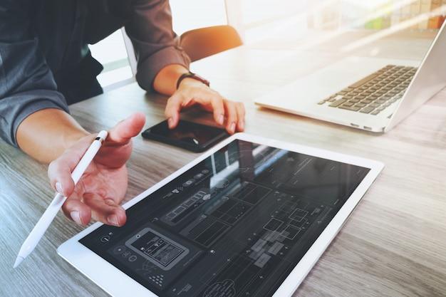 Diseñador de sitios web trabajando tableta digital y computadora portátil y diagrama de diseño digital Foto Premium