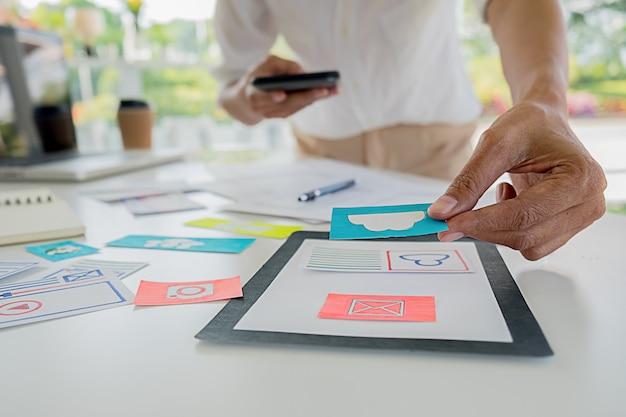 El diseñador web creativo planea la aplicación y desarrolla el diseño de plantillas, marco para teléfonos móviles. concepto de experiencia de usuario (ux). Foto Premium