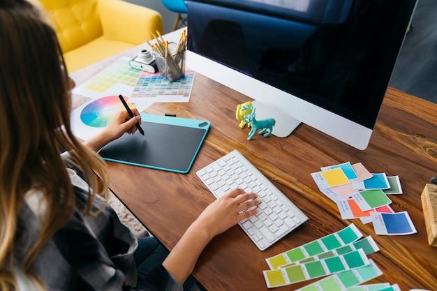 Diseñadora gráfica trabajando en escritorio Foto gratis