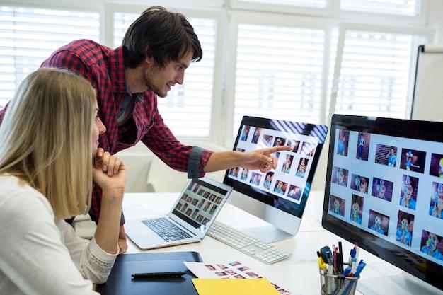 Diseñadores gráficos masculinos y femeninos que interactúan sobre la computadora Foto gratis