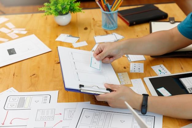 Los diseñadores gráficos trabajan junto con el marco de diseño de la plantilla de la aplicación de planificación del diseñador ux ui para el teléfono móvil, la computadora móvil Foto Premium
