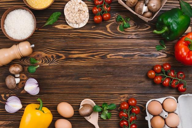 Diseño creativo hecho de verduras frescas y granos de arroz en el escritorio de madera Foto gratis