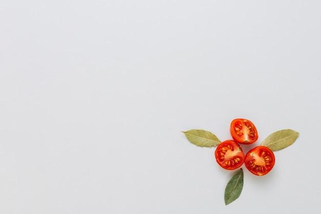 Diseño hecho con hojas de laurel aromáticas y tomates cherry cortados por la mitad en la esquina de fondo blanco Foto gratis