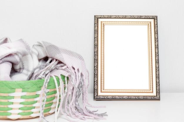 Diseño interior minimalista con marco de fotos y una canasta con ropa de lana cálida en un escritorio Foto Premium