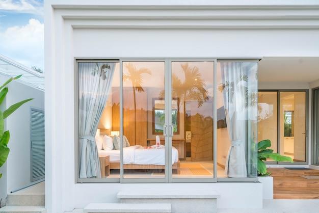 Diseño de interiores de lujo en el dormitorio de la villa de la piscina con techos altos y rosas en la cama en la casa o edificio de la casa Foto Premium