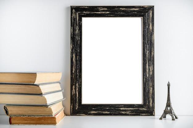 Diseño de marco negro. juegue la torre y los libros viejos cerca del marco en un fondo blanco. Foto Premium