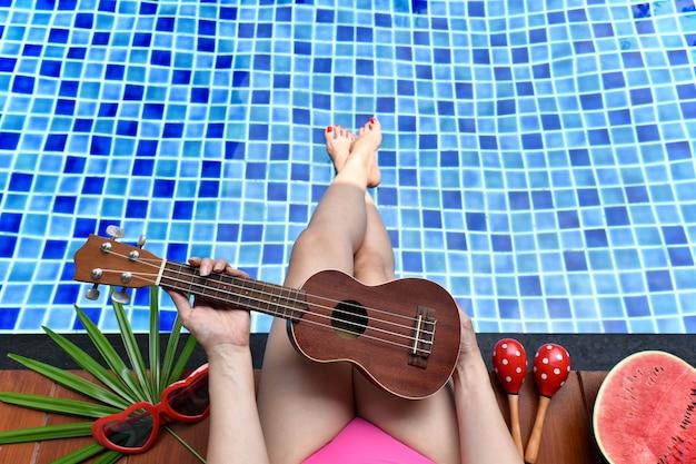 Disfrute de la brisa de verano, chica relajándose cerca de la piscina con fruta de sandía Foto Premium