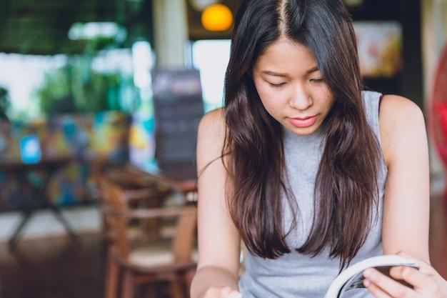 Disfrute de momentos de relax con el libro de lectura, las mujeres asiáticas tailandesas adolescentes se centran seriamente en leer el libro de bolsillo en la cafetería por la mañana tono de color vintage Foto Premium