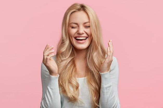 Disparo aislado de alegre joven rubia linda se ríe alegremente mientras escucha una anécdota divertida de un amigo, tiene el pelo largo y claro, posa contra la pared rosa. concepto de felicidad y emociones positivas Foto gratis