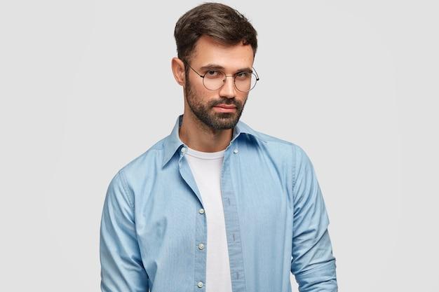 Disparo aislado de hombre caucásico sin afeitar serio confiado mira a través de gafas redondas, vestido con camisa azul de moda, aislado sobre la pared blanca. personas, pensamientos, concepto de estilo de vida Foto gratis