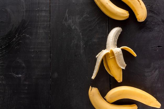 Disparo de alto ángulo de plátanos con un espacio de copia sobre un fondo negro Foto gratis
