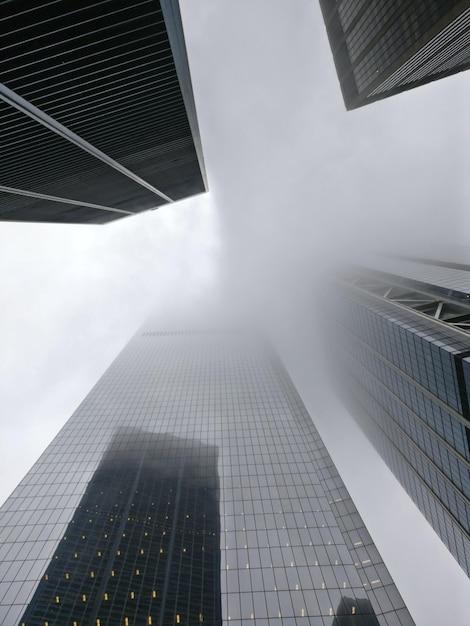 Disparo de ángulo bajo vertical de un bloque de pisos envuelto en niebla Foto gratis