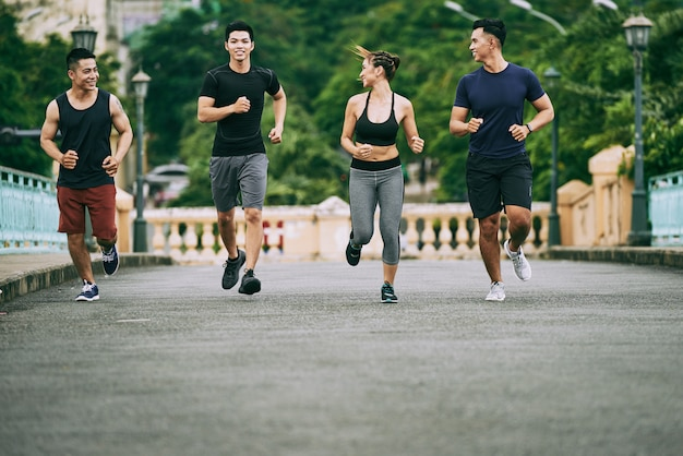 Disparo de cuatro personas corriendo por la mañana. Foto gratis