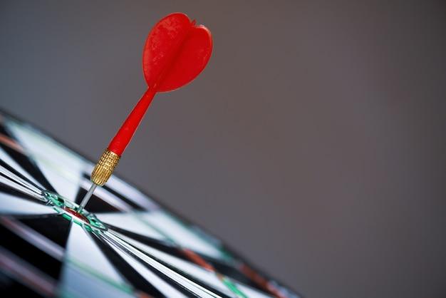 Disparó dardos rojos flechas en el centro de destino sobre fondo oscuro. concepto de objetivo empresarial. Foto Premium
