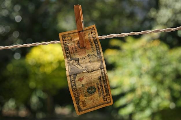 Disparo de enfoque selectivo de un billete colgado de un cable con una pinza para la ropa Foto gratis