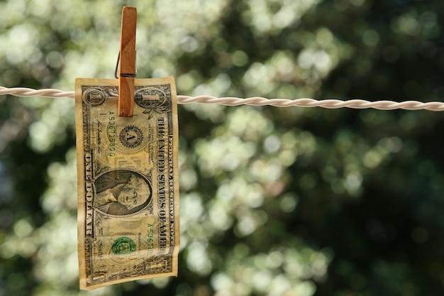 Disparo de enfoque selectivo de un billete de un dólar colgado de un cable con una pinza para la ropa Foto gratis
