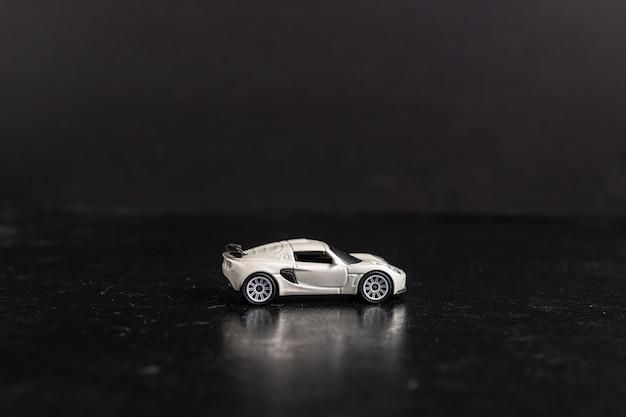 Disparo de enfoque selectivo de un coche deportivo de juguete blanco sobre una superficie negra Foto gratis