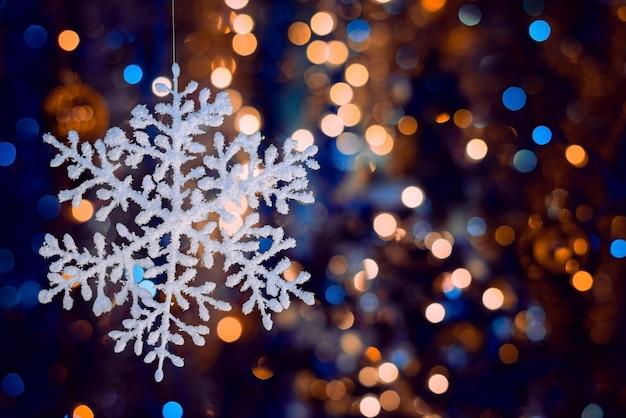 Disparo de enfoque selectivo de un copo de nieve decorativo sobre fondo bokeh borrosa Foto gratis