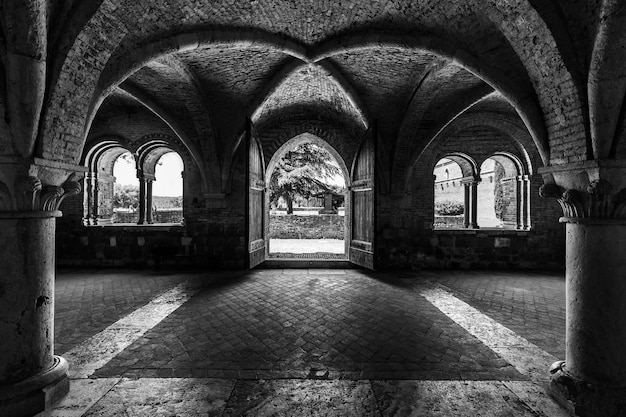 Disparo en escala de grises dentro de la abadía de san galgano en toscana italia con diseño de paredes de arco Foto gratis