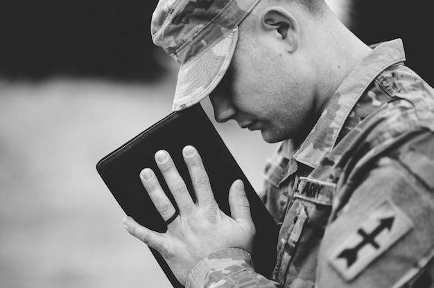 Disparo en escala de grises de un joven soldado rezando mientras sostiene la biblia Foto gratis