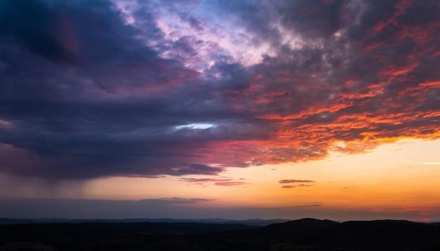 Disparo de gran angular de varias nubes en el cielo durante el atardecer pintado en varios colores Foto gratis