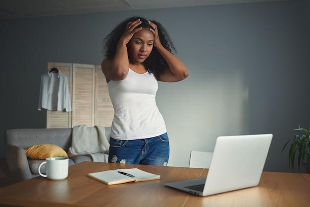 Disparo horizontal de desesperada joven afroamericana independiente tomados de la mano en la cabeza, sintiéndose estresada y en pánico debido a la fecha límite o problema de la computadora, de pie en el escritorio con la computadora portátil abierta Foto gratis
