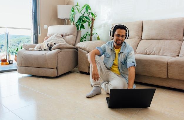 Disparo horizontal de un hombre sentado en el suelo escuchando música y trabajando con un portátil en casa Foto gratis