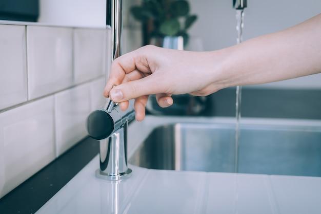 Disparo horizontal de una mano humana abriendo el fregadero moderno para el flujo de agua Foto gratis