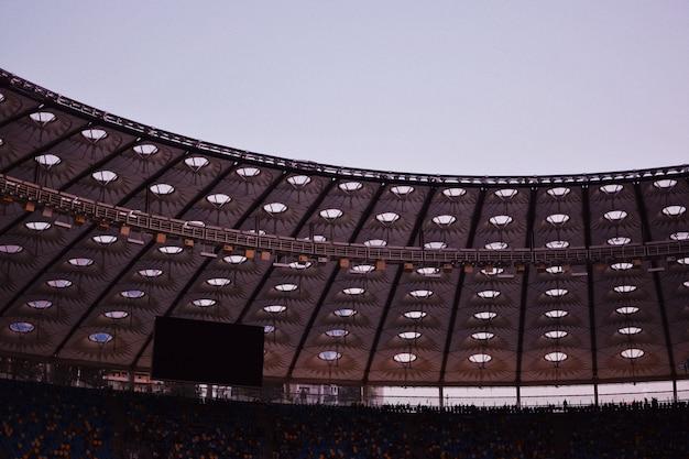 Disparo parcial de un estadio que muestra el techo, un monitor grande en la parte superior de las filas de asientos y sillas Foto gratis
