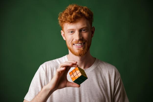Disparo de primer plano del joven barbudo con cabeza lectora sonriente, sosteniendo el cubo de rubik Foto gratis