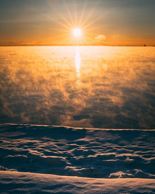 Disparo vertical de un cielo rojo por la mañana en un día de nieve Foto gratis
