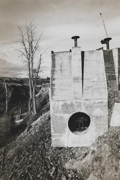 Disparo vertical de un edificio en la colina con un cielo nublado en el fondo en blanco y negro Foto gratis