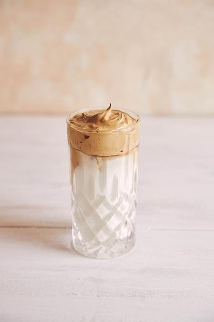 Disparo vertical de un moderno delicioso café dalgona fresco con leche sobre una mesa de madera blanca Foto gratis