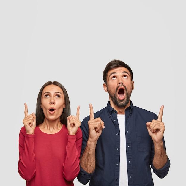 Disparo vertical de una mujer caucásica sorprendida y un hombre apuntando con ambos dedos índices hacia arriba, muestra el espacio libre para la promoción Foto gratis