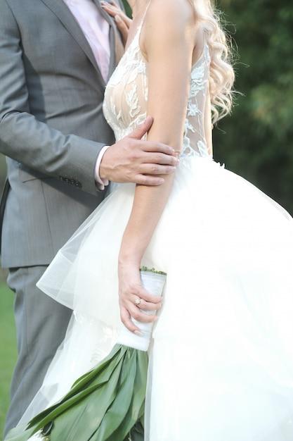 Disparo vertical del novio y la novia posando para una sesión de fotos de boda romántica Foto gratis