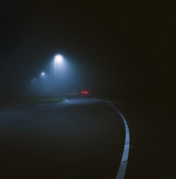 Disparo vertical de un poste de luz por la calle capturado durante la noche Foto gratis
