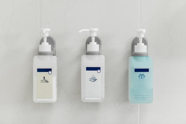 Dispensadores de jabón líquido en la pared gris. Foto Premium