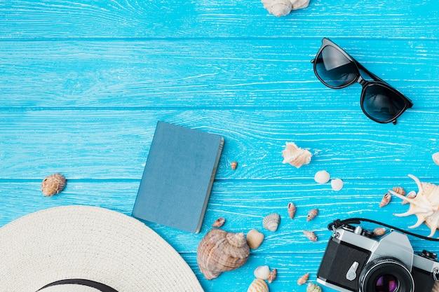 Disposición de conchas cerca de cámara retro y gafas de sol con sombrero Foto gratis