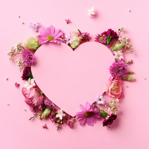 Disposición creativa con las flores rosadas, corazón de papel sobre fondo en colores pastel punchy. tarjeta del día de san valentín. corazón de cutted en fondo de papel en colores pastel punchy. Foto Premium