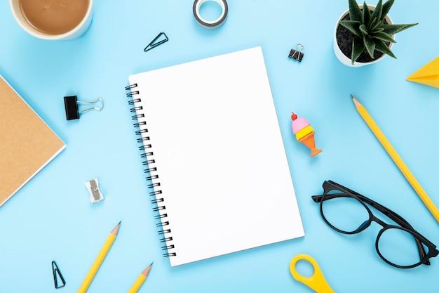 Disposición plana de elementos de escritorio sobre fondo azul. Foto gratis
