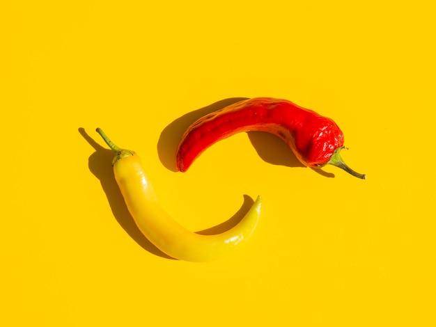 Disposición plana con pimientos picantes y fondo amarillo. Foto gratis