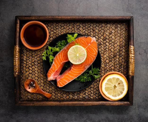 Disposición plana con salmón y limón. Foto gratis