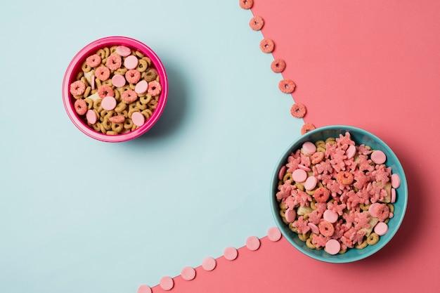 Disposición plana con tazones de cereal y fondo colorido Foto gratis
