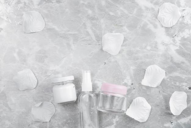 Disposición de productos para el cuidado de la cara plana sobre fondo de mármol Foto gratis